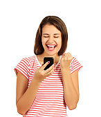 Portrait of a happy joyful girl holding mobile phone and celebrating a win. emotional girl isolated on white background