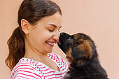 True friendship between girl and puppy who is giving a kiss