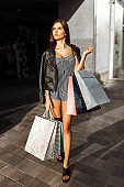 Beautiful stylish girl with bags walking down the street, after shopping, holding bags, outdoors