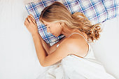 Young girl sleeping in bed. Portrait of a woman resting on a comfortable bed with pillows in white bedding in the morning.