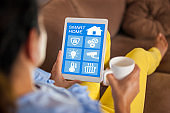 Woman holding tablet with app smart home screen living room