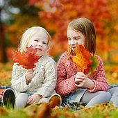 Two sisters having fun together in autumn park