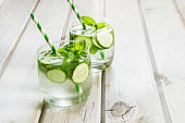 Summer refreshing detox cocktail. Water with cucumber,mint and ice in glass on a white wooden board. Rustic style.