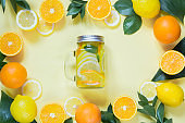 Summer refreshing cocktail with lemon, orange, mint and ice in mason jar on yellow. Tropical concept.