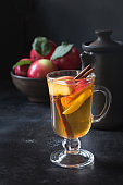 Apple tea with lemon, spiced and cinnamon on black board. Close up. Autumn still life.