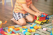 Little Asian child playing with lots of colorful plastic blocks indoor. Kid boy wearing colorful shirt and having fun with building and creating.