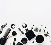 Flat Lay, Beauty blog concept. Female make up accessories on white background. top view of black trendy fashion feminine background.