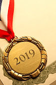 Gold Medal Inscribed With '2019' Resting On An Award Certificate