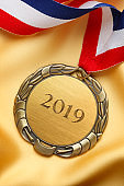 2019 Engraved On Gold Medal Resting On Gold Colored Satin