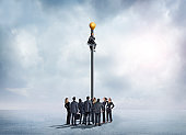 Group Of Business People Look Up At Businessman Clinging To A Tall Flagpole