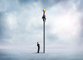Businesswoman Looks At Businessman Clinging To A Tall Flagpole