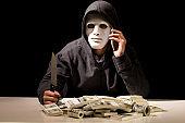 Hacker in a hood on dark background