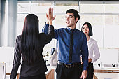 Successful business team giving a high fives gesture at office