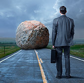 Businessman Stands Looking At Large Boulder Blocking His Path In Middle Of Road