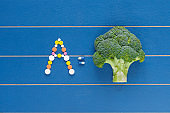 Powerful antioxidant of broccoli as the most concentrated source of vitamin A. Broccoli on blue wooden background. Various colorful tablets and pills have shape of the letter A. Top view