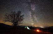 Night camping in the mountains. Hikers having a rest in tourist tent under starry sky near campfire
