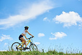 Back view of athlete young biker riding on yellow mountain bike against blue sky with clouds, Woman wearing helmet, enjoying valley view on sunny day. Outdoor sport activity. Copy space