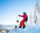Man snowboarder sitting on top of a snowy hill with his snowboard enjoying stunning mountains view ski resort