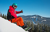 Snowboarder sitting, relaxing on the snowy slope at winter ski resort in the mountains, showing thumbs up