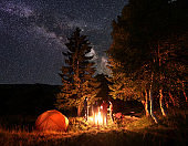 Group of friends warm their hands around campfire in woods near tent under an unusually starry sky