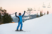 Girl enjoying ski holiday standing on the snowy mountain and raised her hands up