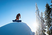 Low angle shot of a freerider snowboarder walking up the slope in the mountains