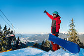 Full length shot of a snowboarder standing on the top of the mountains, showing thumb up, enjoying beautiful winter day