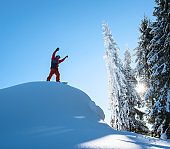 Snowboarder freerider standing on top of the ski slope with his arms in the air in victorious gesture in the mountains