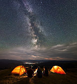 Back view travel team sitting near fire beside camping in night under wonderfull sky with many stars