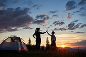 Silhouette of young woman and child giving each other high five near camping at dawn on top of mountain