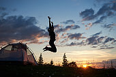 Happy girl jumping on grass with wildflowers at camping in mountains at dawn under blue sky