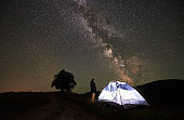 Woman tourist resting at night camping under starry sky and Milky way
