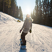 Rearview shot of a snowboarder riding the slope in the mountains on a beautiful winter sunny day