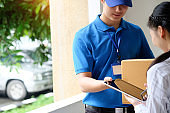 Woman appending signature sign on tablet after accepting receive boxes from delivery man, woman sign on digital tablet, receive delivery concept