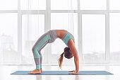 Beautiful woman practices backbend yoga asana Urdhva Dhanurasana - Upward facing bow pose at the yoga studio