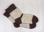 male grey knitted socks made of dog hair  on grey background close up, top view