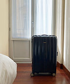 Suitcase by white window