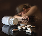 Depressed woman with a bottle of pills