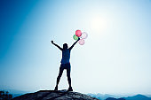 Freedom woman on sunrise mountain top edge with balloons