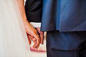 Close-up photo of wedding couple holding hands.