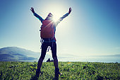 happy woman hiker on beautiful green mountain hill top