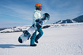 one snowboarder with snowboard walking on the snowobard piste in winter mountains