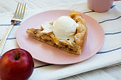 Slice of home-baked apple pie with ice cream on pink plate. Closeup.