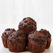 Homemade chocolate cupcakes on white wooden background, side view. Closeup.
