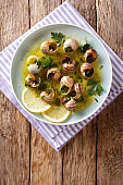 French cuisine: Escargot with butter, herbs and garlic close-up on a plate. horizontal top view