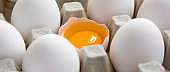 Cracked egg among other chicken eggs in carton egg box, close-up.
