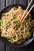 Delicious soba with vegetables and sesame close-up on a plate. Vertical top view
