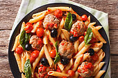 Italian Food: Pasta with meatballs, olives and tomato sauce closeup. Horizontal top view