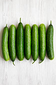 Flat lay of raw organic green cucumbers on white wooden background. Top view, from above, overhead.