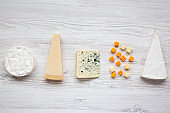 Assortment of different cheese on a white wooden background. From above, flat lay.